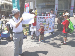 2015 年 7月 20 日桜木町駅前戦争法反対宣伝で訴える栖原事務局長